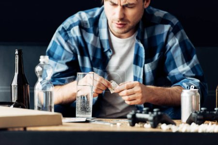 Photo for Man suffering from hangover holding aspirin and looking at glass of water - Royalty Free Image