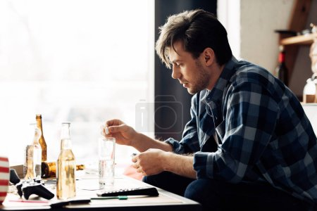 Photo for Tired man putting aspirin in glass of water in messy living room - Royalty Free Image