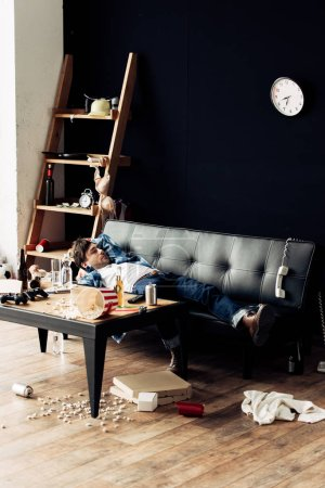 Photo for Tired man lying on sofa after party in messy living room - Royalty Free Image