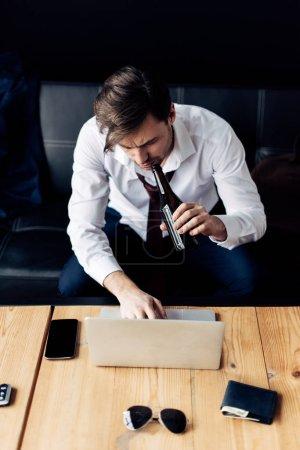 Photo pour Homme en costume tenant bouteille et dactylographier sur ordinateur portable après la fête - image libre de droit
