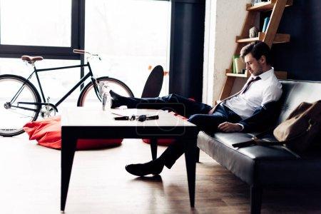Foto de Hombre en traje de dormir en el sofá después de fiesta en la oficina - Imagen libre de derechos
