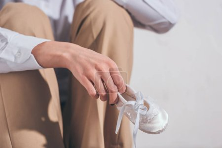 Photo pour Cropped view of woman in beige pants holding baby shoe and sitting on white background in room, grieving disorder concept - image libre de droit