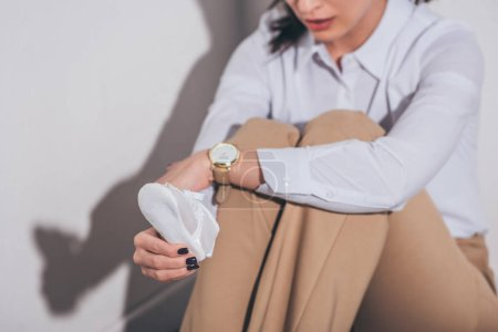 Photo for Cropped view of sad woman in white blouse and beige pants sitting on floor near  wall and holding baby shoe at home, grieving disorder concept - Royalty Free Image