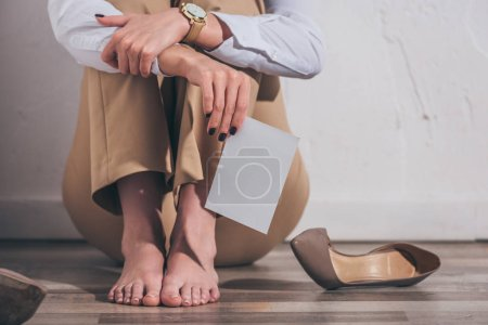 Photo for Cropped view of woman sitting on floor, holding photo near shoes and white wall at home, grieving disorder concept - Royalty Free Image