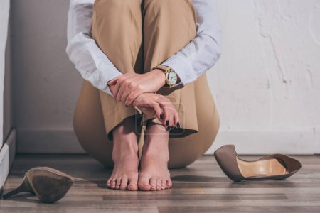 Photo for Cropped view of woman in white blouse and beige pants sitting on floor near wall at home, grieving disorder concept - Royalty Free Image