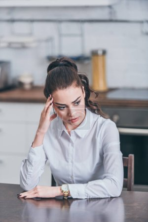 Photo for Upset woman sitting at table and putting hand forehead in kitchen, grieving disorder concept - Royalty Free Image