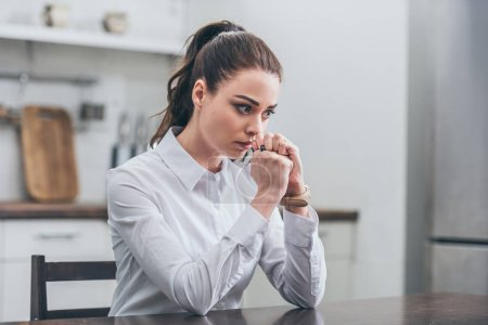 Photo for Upset woman in white blouse sitting at table in kitchen and thinking, grieving disorder concept - Royalty Free Image