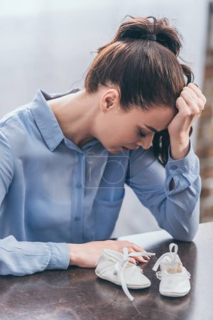 Photo for Sad woman in blue blouse sitting at wooden table with baby shoes and crying at home, grieving disorder concept - Royalty Free Image