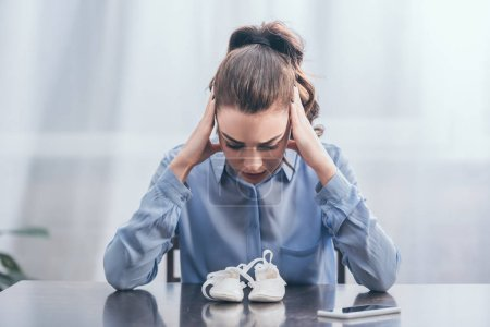Photo pour Sad woman in blue blouse sitting at wooden table with smartphone and looking at white baby shoes at home, grieving disorder concept - image libre de droit