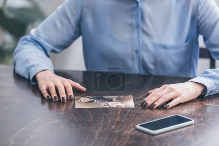 Photo pour Cropped view of woman in blue blouse sitting at wooden table with smartphone and photo at home, grieving disorder concept - image libre de droit