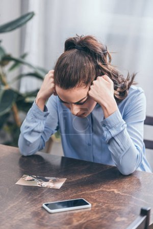 Photo for Sad woman in blue blouse sitting at table with smartphone and looking at photo at home, grieving disorder concept - Royalty Free Image