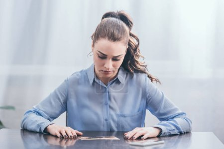 Photo for Upset woman in blue blouse sitting at wooden table with smartphone and looking at photo in room, grieving disorder concept - Royalty Free Image