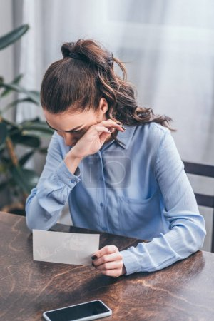 Foto de Upset woman in blue blouse sitting at table with photo, smartphone and crying at home, grieving disorder concept - Imagen libre de derechos