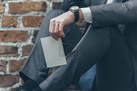 Foto de Cropped view of man in grey suit sitting and holding photo on brown textured background in room, grieving disorder concept - Imagen libre de derechos