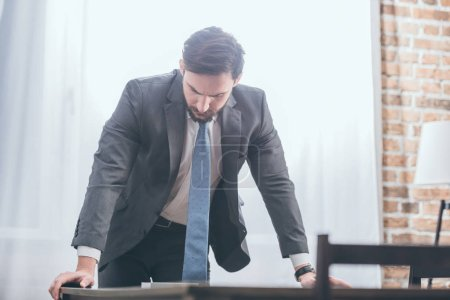 Photo for Sad man in gray suit standing near table and looking at photo in frame at home, grieving disorder concept - Royalty Free Image