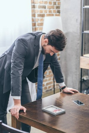Foto de Upset man in gray suit standing near table with smartphone and looking at photo in frame at home, grieving disorder concept - Imagen libre de derechos