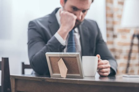 Photo for Selective focus of upset man in gray suit sitting at wooden table, holding white cup and looking at photo frame in room, grieving disorder concept - Royalty Free Image