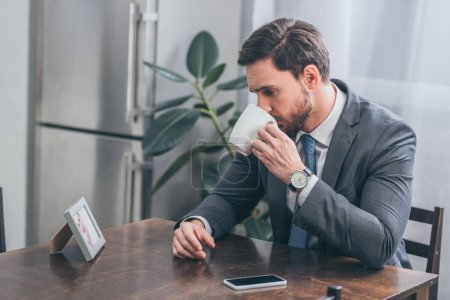 Foto de Sad man in gray suit sitting at wooden table with smartphone drinking and looking at poto in frame at home, grieving disorder concept - Imagen libre de derechos