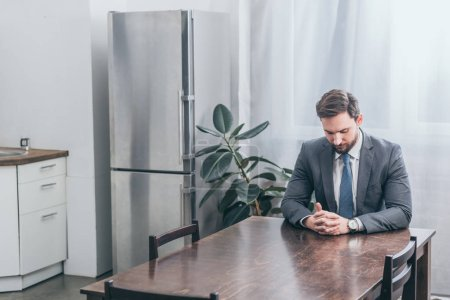 Photo for Upset man in gray suit sitting at wooden table and thinking in kitchen, grieving disorder concept - Royalty Free Image