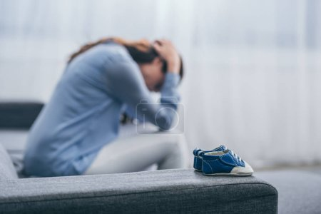 Photo for Selective focus of blue baby shoes on couch with sad woman sitting and lowering head at home, grieving disorder concept - Royalty Free Image