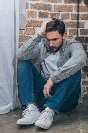 upset man in grey shirt and blue pants sitting on floor on brown textured background in room, grieving disorder concept