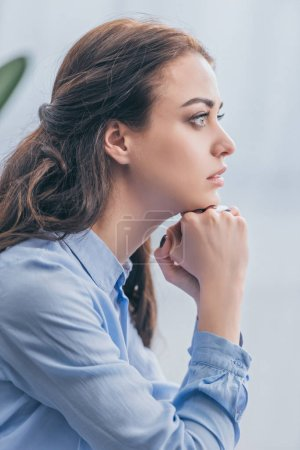 Photo for Sad woman in blue blouse sitting and looking into distance at home, grieving disorder concept - Royalty Free Image
