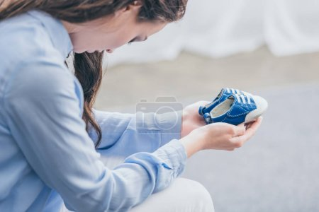 Foto de Cropped view of sad woman in blue blouse sitting and holding baby shoes at home, grieving disorder concept - Imagen libre de derechos