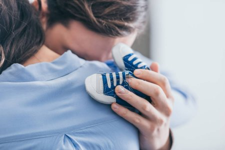 Photo pour Cropped view of man hugging woman and holding blue baby shoes in room, grieving disorder concept - image libre de droit