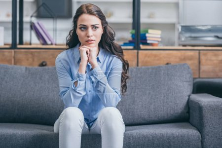 Photo for Sad woman in blue blouse and white pants sitting on grey couch in kitchengrieving disorder concept , - Royalty Free Image