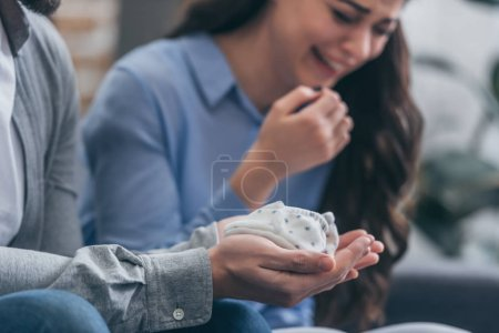 Foto de Cropped view of man holding baby socks while woman crying at home, grieving disorder concept - Imagen libre de derechos