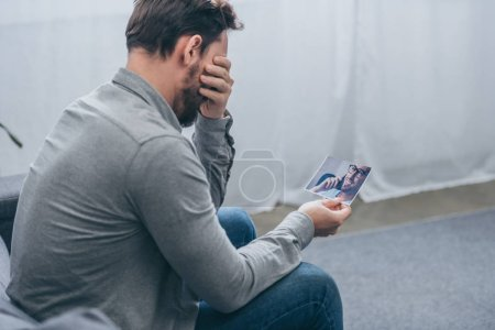 Photo for Man sitting and crying while holding a male portrait at home, grieving disorder concept - Royalty Free Image