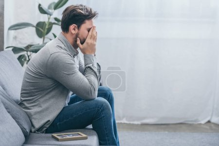 Photo for Man sitting on grey couch with photo in frame and crying at home, grieving disorder concept - Royalty Free Image