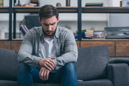 Photo for Depressed man sitting and grieving on couch in living room - Royalty Free Image