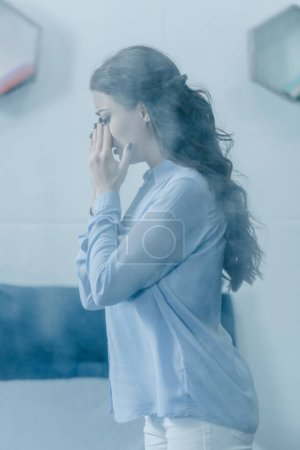 Photo for Selective focus of depressed woman covering face with hands and crying at home - Royalty Free Image