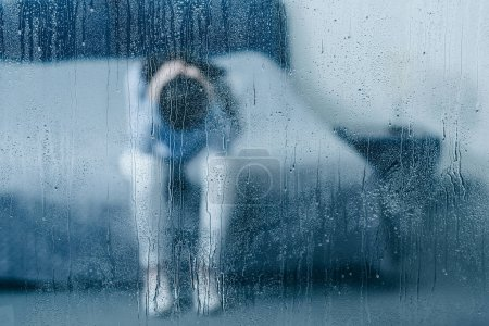 Photo for Depressed woman sitting on bed and holding head in hands through window with raindrops - Royalty Free Image