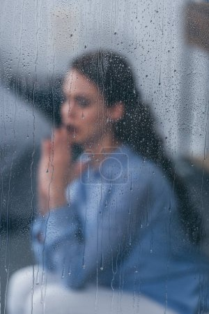 Photo for Selective focus of raindrops on windows with sad woman sitting and praying on background - Royalty Free Image