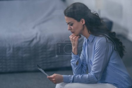 Photo for Grieving woman propping chin and looking at photograph at home with copy space - Royalty Free Image