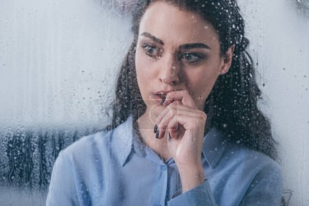 Photo for Beautiful upset woman touching face and looking through window with raindrops - Royalty Free Image