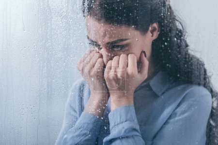 Photo for Depressed woman covering face with hands and crying at home through window with raindrops - Royalty Free Image