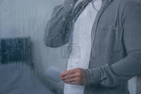 Photo for Cropped view of man holding photograph through window with raindrops - Royalty Free Image