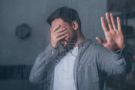 Photo for Upset man covering face with hand, crying and touching window with raindrops - Royalty Free Image