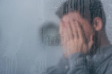 Photo for Selective focus of raindrops on window with man covering face and crying on background - Royalty Free Image