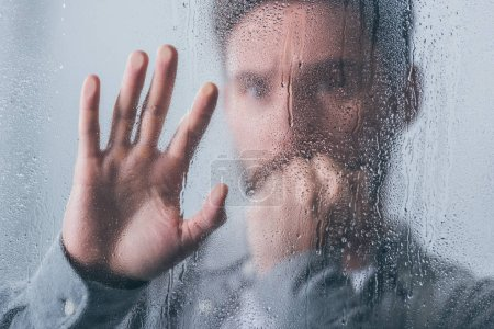 Photo for Upset man covering mouth with hand and touching window with raindrops - Royalty Free Image