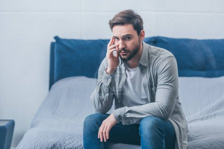 Photo for Depressed man sitting on bed, looking at camera and grieving at home - Royalty Free Image