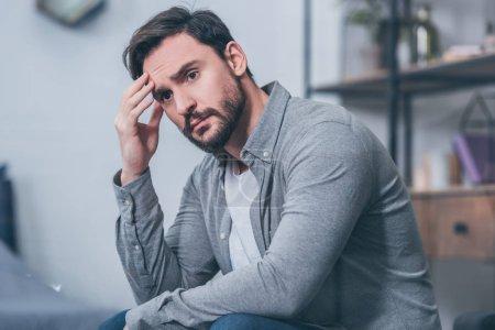 Foto de Enfoque selectivo de hombre molesto guapo sentado, tocando la cara y el duelo en casa - Imagen libre de derechos
