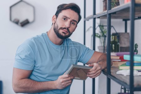 Photo for Selective focus of upset man holding photo frame and looking at camera at home - Royalty Free Image