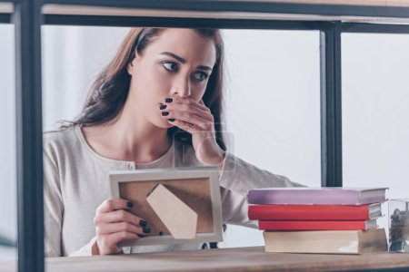 Photo for Grieving woman covering mouth with hand while holding picture frame at home - Royalty Free Image
