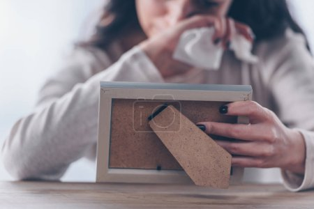 Photo for Cropped view of upset woman holding picture frame and crying at home - Royalty Free Image