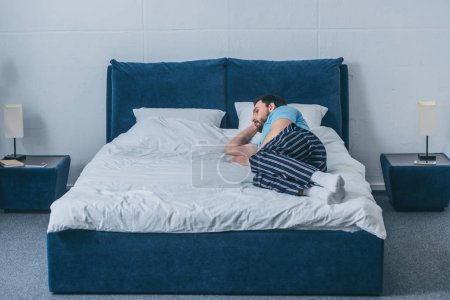 Photo for Sad lonely man lying in bed at home with copy space - Royalty Free Image