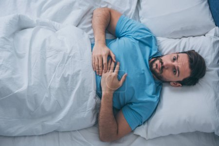Photo for Top view of sad lonely man looking at camera and lying in bed at home - Royalty Free Image